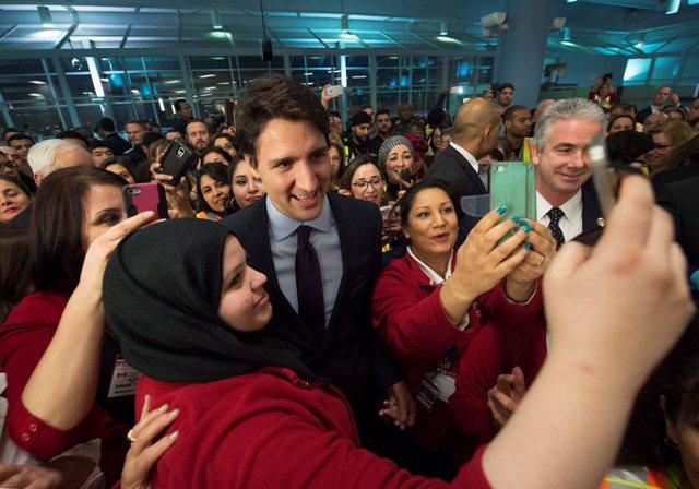 Na snímke kanadský premiér  Justin Trudeau (uprostred) sa fotí pred príletom  sýrskych utečencov na letisku v Toronte