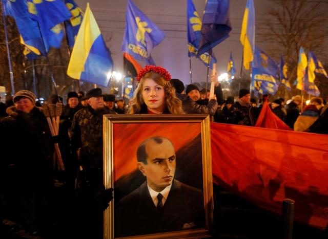 Ukrajinskí nacionalisti s portrétom Stepana Banderu počas fakľového pochodu v centre Kyjeva v piatok  1. januára 2016