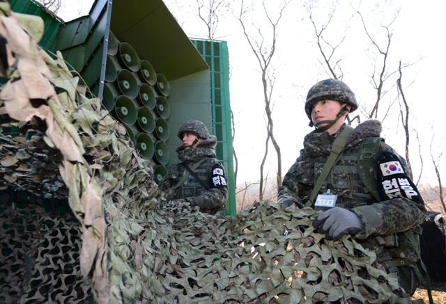 Juhokórejskí vojaci dávajú dole maskovanie zo zariadenia na vysielanie propagandy cez amplióny pri hranici so Severnou Kóreou v Jienčchone