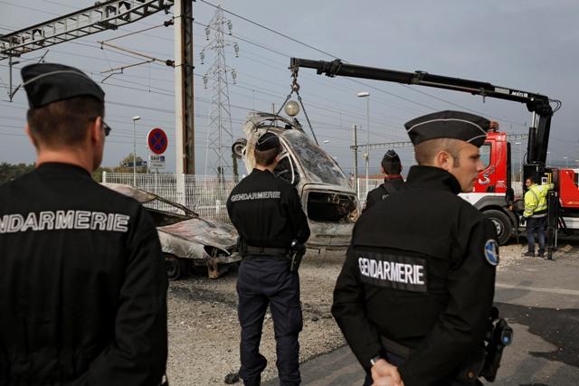 Žeriav dvíha vrak podpáleného auta za asistencie polície po násilných nepokojov, ktoré vypukli v utorok 20. októbra 2015 v meste Moirans na území východofrancúzskeho departementu Isere