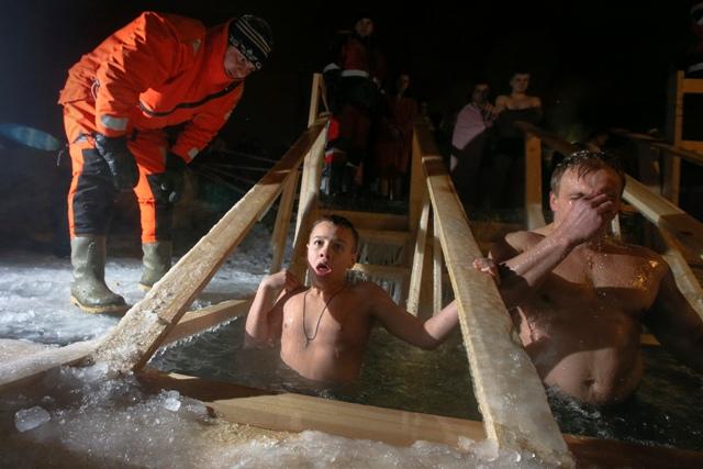 Na snímke záchranár kontroluje pravoslávnych veriacich, ktorí sa ponárajú do ľadovej vody v rybníku počas sviatku Zjavenia Pána 19. januára 2016 v ruskom meste Krasnoje Selo neďaleko Petrohradu
