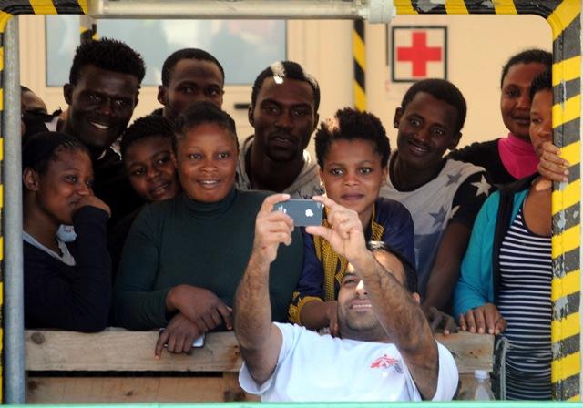 """Člen posádky lode Lekárov bez hraníc s názvom  """"Bourbon Argos"""" sa fotí s migrantmi pred príchodom do prístavu Vibo Valentia 23. augusta 2015"""