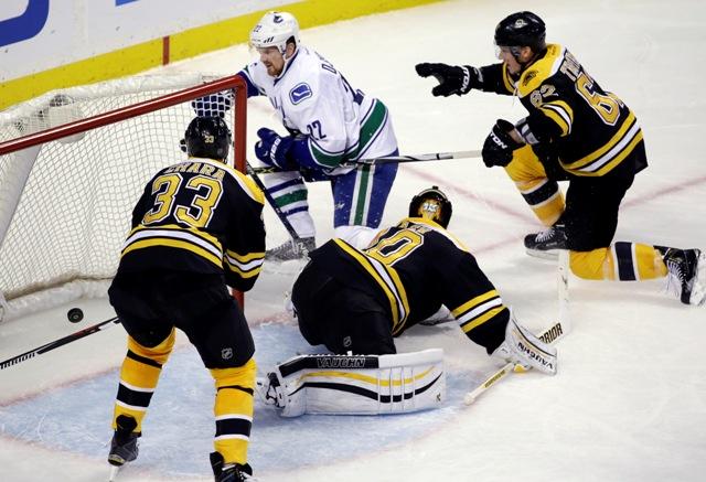 Na snímke vľavo slovenský obranca Bruins Zdeno Chára, druhý zľava v pozadí hráč Canucks Daniel Sedin strieľa gól, uprostred brankár Bruins Tuukka Rask a vpravo jeho spoluhráč Zach Trotman v zápase hokejovej NHL Boston Bruins - Vancouver Canucks