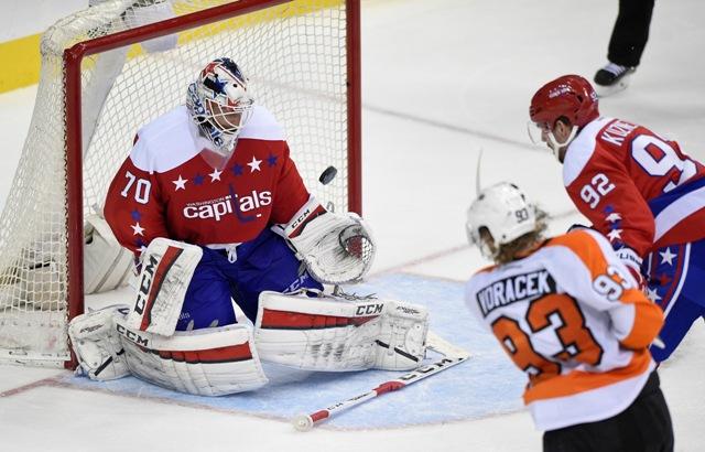 Brankár Capitals Braden Holtby pozerá na puk, ktorý do siete jeho bránky vyslal v predĺžení český útočník Flyers Jakub Voráček (vpravo dole) v zápase hokejovej NHL Philadelphia Flyers - Washington Capitals