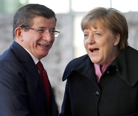 Na snímke nemecká kancelárka Angela Merkelová (vpravo) si podáva ruku s tureckým premiérom Ahmetom Davutogluom