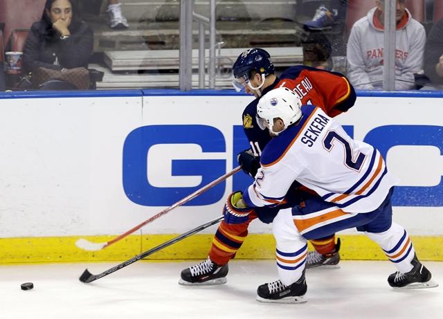 Na snímke obranca Edmontonu Oilers Slovák Andrej Sekera (vpravo) a hráč Floridy Panthers  Jonathan Huberdeau bojujú o puk v zápase zámorskej hokejovej NHL Florida Panthers - Edmonton Oilers