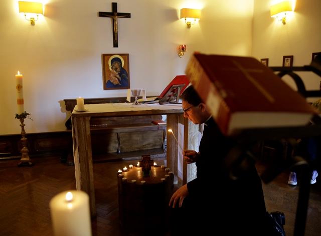Na snímke duchovný Marcus Walker zapaľuje sviečky na pamiatku 148 obetí útoku islamistickej skupiny aš-Šabáb na študentov a zamestnancov univerzity v Garisse