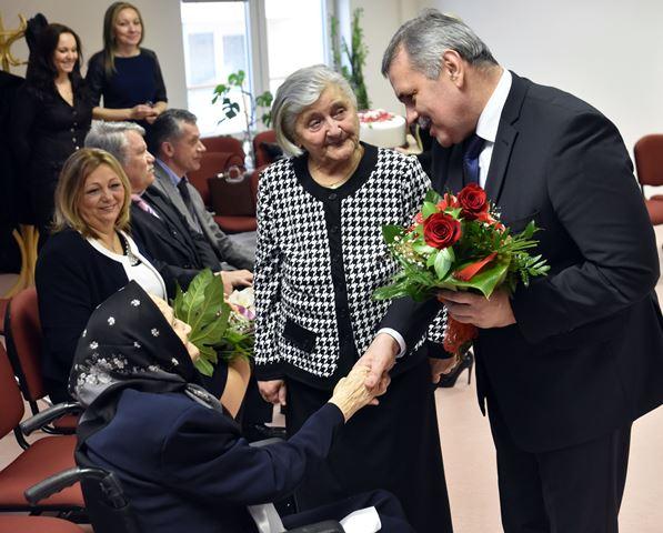 Na snímke vľavo dole Helena Gáborová, oslávenkyni gratuluje primátor Micahloviec Viliam Záhorčák (vpravo)