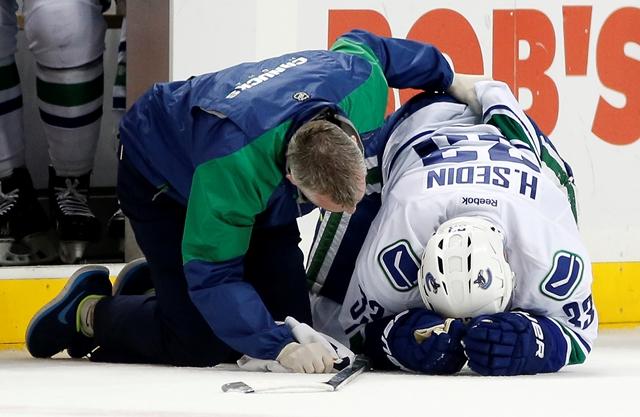 Na snímke fyzioterapeut sa skláňa nad hokejistom Vancouveru Canucks Henrikom Sedinom, ktorý kľačí na ľade v prvej tretine zápasu zámorskej hokejovej NHL proti New Yorku Islanders v New Yorku