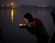 Indický hinduista sa modlí pred tým, ako položí na vodu plávajúci kahanec s kvetmi veèer na brehu rieky Gangy