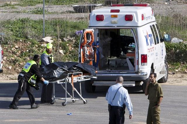Na snímke izraelskí záchranári odvážajú telo zabitého palestínskeho útočníka na mieste útoku