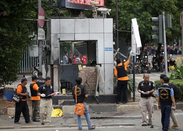 Na snímke policajní dôstojníci skúmajú trosky po výbuchoch a streľbe v centre indonézskej Jakarty
