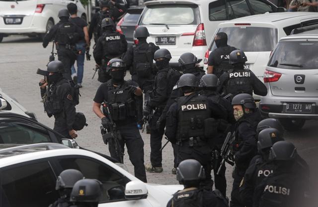 Na snímke indonézski policajti na mieste bombových útokov a streľby v centre indonézskej Jakarty