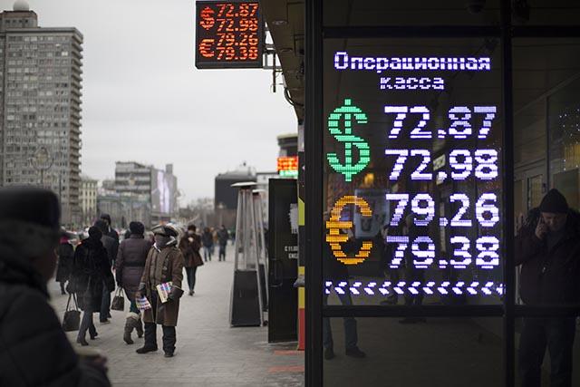 Na snímke zmenáreň v Moskve s kurzmi rubľa voči doláru a euru (31. december 2015).