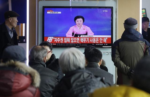 """Na snímke ľudia v Južnej Kórei sledujú televízny program, v ktorom hlásateľka priniesla správu o testovaní nukleárnej bomby. Na obrazovkách prebieha text: """"Nepoužijeme nukleárnu silu, keď bude zachovaná naša autonómia."""""""