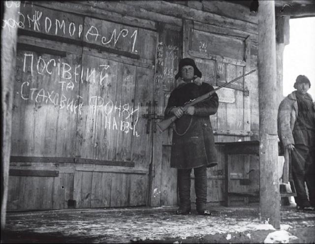 Komsomolec a pracovník kolchozu strážia osevné a rezervné fondy. Dedina Oľšana. Charkovská oblasť. 1933