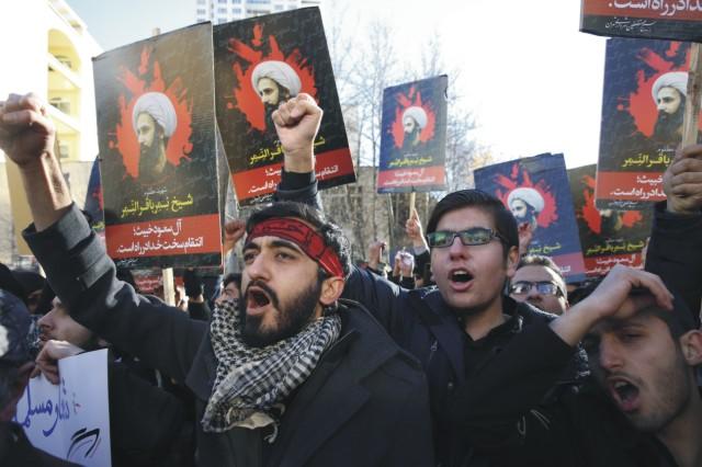 Demonštranti skandujú a držia portréty významného saudského šiitského duchovného Nimra an-Nimra počas protestu proti jeho poprave