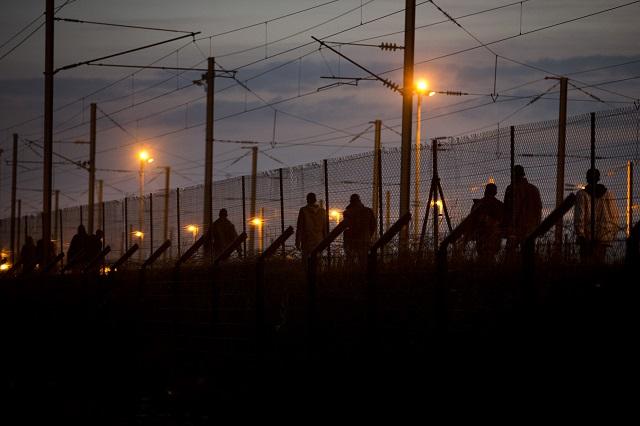 Africkí migranti kráčajú po tom, ako prekročili plot pri pokuse prejsť k tunelu pod Lamanšským prielivom vo francúzskom Calais