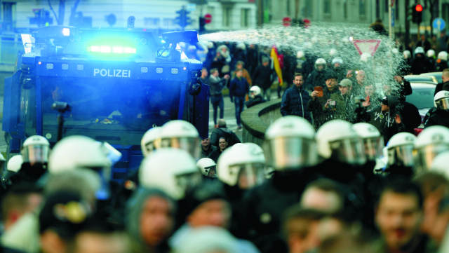 Na archívnej snímke sa polícia snaží rozohnať ľudí, ktorí protestujú po Silvestrovských udalostiach  pred hlavnou policajnou stanicou v Kolíne nad Rýnom Na archívnej snímke ľudia držia počas protestu transparenty po Silvestrovských udalostiach pred hlavnou policajnou stanicou v Kolíne nad Rýnom