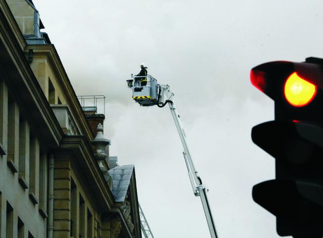 asič na požiarnom rebríku sa snaží dostať ku streche luxusného hotela Ritz počas požiaru v Paríži