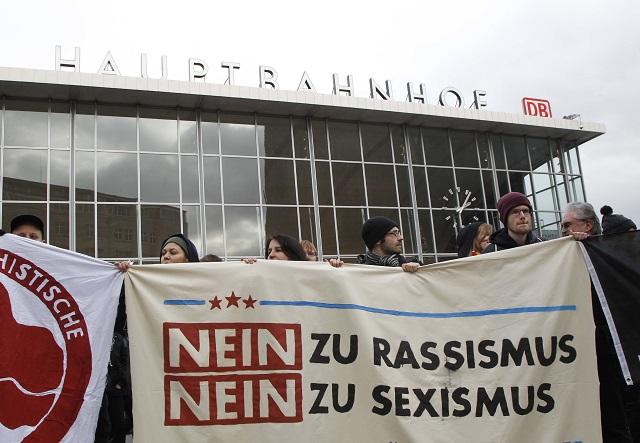 Ľudia držia transparent s nápisom Nie rasizmu, Nie sexizmu počas protestu pred hlavnou policajnou stanicou v Kolíne nad Rýnom