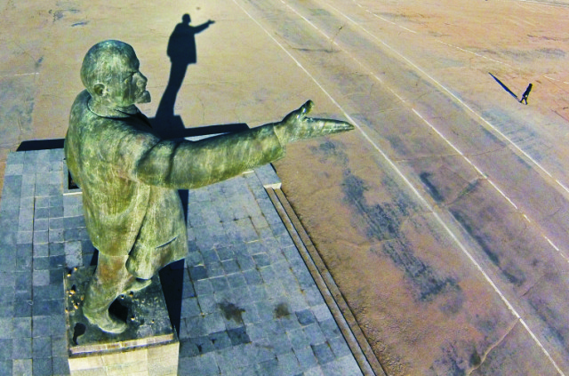 Na snímke žena kráča neďaleko sochy bolševického vodcu a zakladateľa bývalého Sovietskeho zväzu Vladimira Iľjiča Lenina