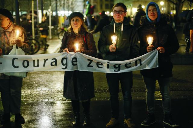"""Ľudia držia sviečky na protest proti konaniu demonštrácie proti islamizácii Západu skupiny LEGIDA, ktorá je úzko prepojená s hnutím PEGIDA v Lipsku na východe Nemecka 11. januára 2016. Na transparente je nápis """"Ukážte odvahu"""""""