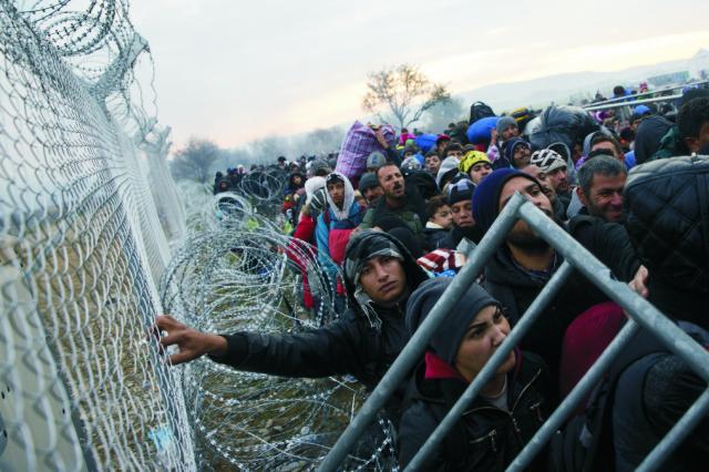 Na snímke migranti a utečenci čakajú pri plote na grécko-macedónskej hranici v snahe prejsť do Macedónska v Idomeni