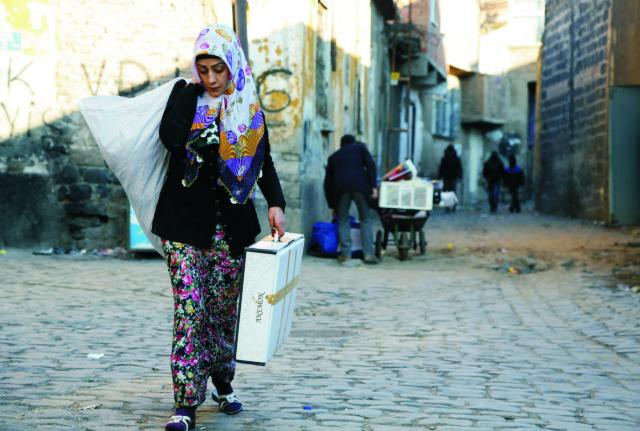 Ľudia utekajú so svojím majetkom z historickej štvrte Sur, ktorá sa nachádza v prevažne kurdskom meste Diyarbakir na juhovýchode Turecka po rozšírení zákazu vychádzania