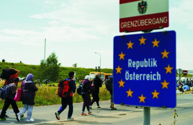 Na archívnej znímke utečenci prechádzajú cez hranice medzi Rakúskom a Maďarskom neďaleko rakúskej obce Heiligenkreuz im Lafnitztal