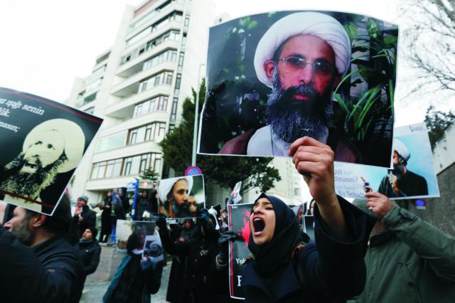 Na snímke protestujúci ľudia držiaci podobizeň popraveného popredného šiitského duchovného Nimra an-Nimra. Poprava sa uskutočnila v sobotu 2. januára 2016 v Saudskej Arábii