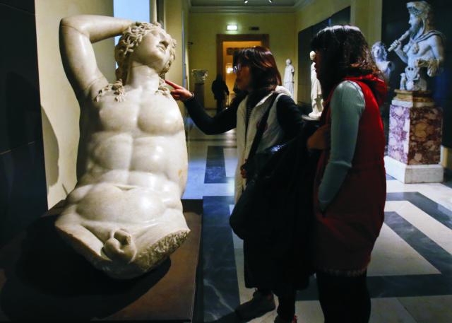 Návštevníčky si prezerajú nahú sochu Dionýsosa, ktorý je v gréckej mytológii synom najvyššieho boha Dia a jeho milenky Semely v Kapitolských múzeách v Ríme