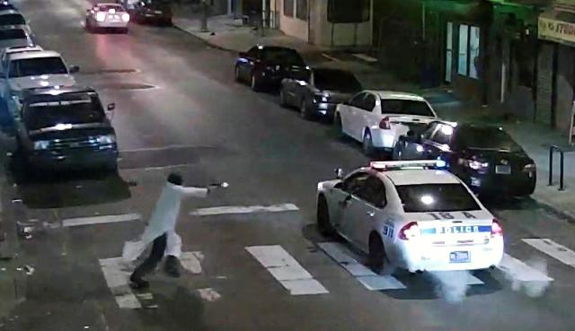 Na snímke muž strieľa na policajta v aute