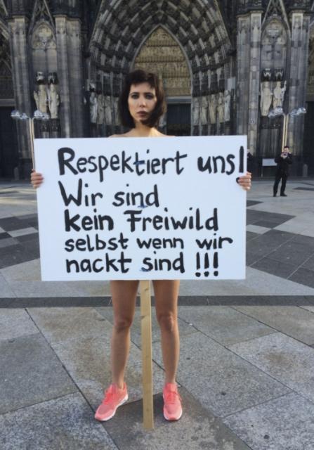 """Švajčiarska umelkyňa Milo Moireová stojí pred kolínskou katedrálou s transparentom, na ktorom je nápis """"Rešpektujte nás. Nie sme štvaná zver, ani keď sme nahé."""" počas dnešného protestu 8. januára 2016. kradnutie, ohrozovanie alebo sexuálne obťažovanie skupinami prevažne opitých mužov vo veku 18-35 rokov počas novoročných osláv v Kolíne nad Rýnom nahlásilo podľa údajov agentúry Reuters 121 žien"""