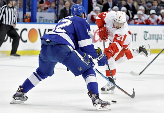 Hokejista Detroitu Red Wings Slovák Tomáš Tatar strieľa cez obrancu Tampy Bay Lightning Andreja Šustra z Českej republiky v zápase zámorskej hokejovej NHL