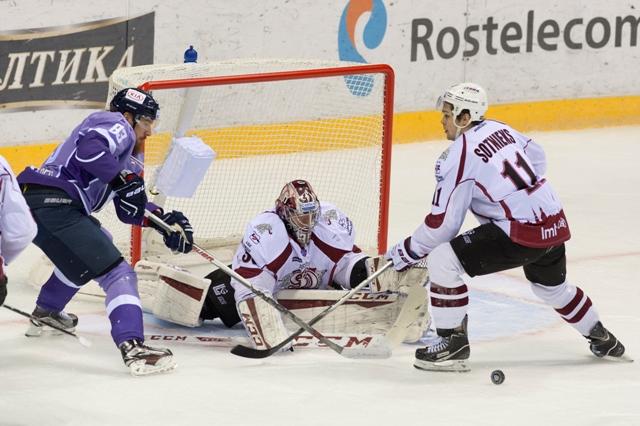 Na snímke zľava Lukáš Kašpar (Slovan), brankár Jakub Sedláček a Kristaps Sotnieks (Dinamo) v hokejovom stretnutí KHL medzi HC Slovan Bratislava - Dinamo Riga