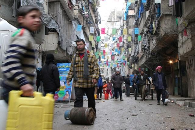 Na snímke snímke z 11. februára 2016 civilný obyvatelia nesú zásoby jedla a vody v sýrskom meste Aleppo