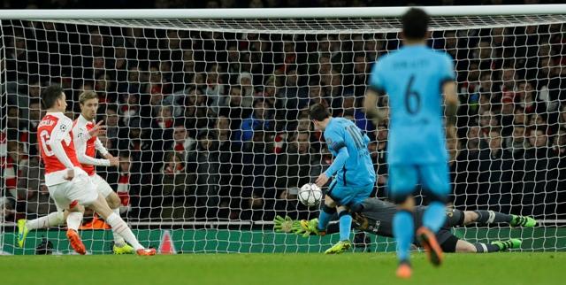 Na snímke uprostred útočník Barcelony Lionel Messi strieľa úvodný gól, dole padajúci český brankár Arsenalu Petr Čech v prvom zápase osemfinále futbalovej Ligy majstrov Arsenal Londýn - FC Barcelona (0:2)