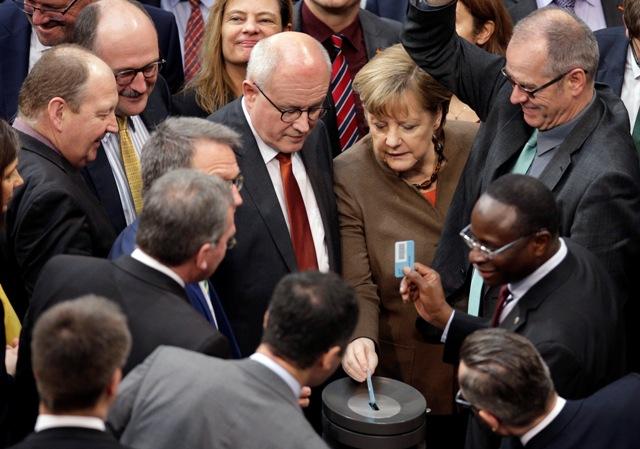 Na snímke uprostred nemecká kancelárka Angela Merkelová hlasuje počas zasadnutia nemeckého Spolkového snemu (Bundestagu) v Berlíne 25. februára 2016