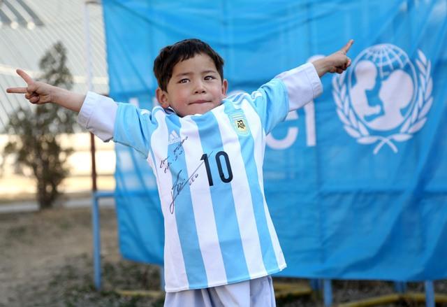 Päťročný afganský chlapec Murtazá Ahmadí, ktorý je veľkým fanúšikom argentínskeho futbalistu Lionela Messiho, ukazuje darovaný a podpísaný futbalový dres od Messiho