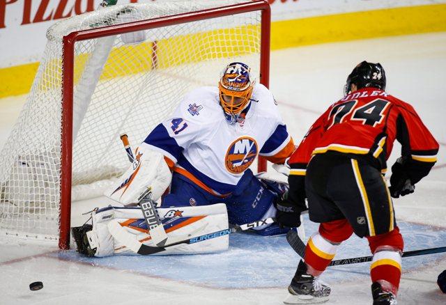 Slovenský brankár Islanders Jaroslav Halák vyráža puk po strele českého útočníka Flames Jiřího Hudlera (vpravo) v zápase v zápase zámorskej NHL New York Islanders - Calgary Flames