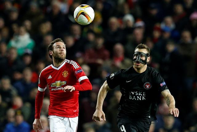 Hráč Manchesteru United Juan Mata (vľavo) bojuje o loptu s Nikolajom Bodurovom z Midtjyllandu vo futbalovom zápase odvety 16-finále Európskej ligy medzi Manchester United - FC Midtjylland