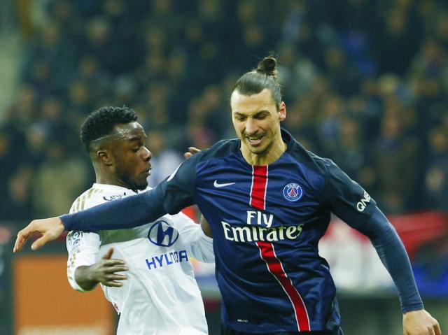 Hráč PSG Zlatan Ibrahimovič (vpravo) a hráč Lyonu Maxwel Cornet v súboji o loptu v zápase 28. kola najvyššej francúzskej futbalovej ligy Paríž Sain Germain -  Olympique Lyon 28. februára 2016 v Paríži