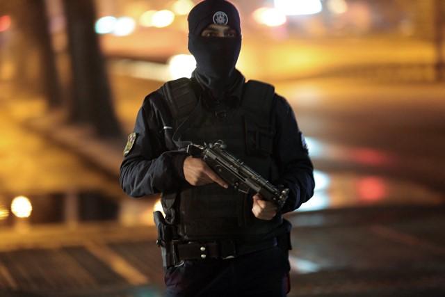 Na snímke ozbrojený policajt stojí pri uzatvorenej hlavnej ceste neďaleko miesta mohutného výbuchu bomby