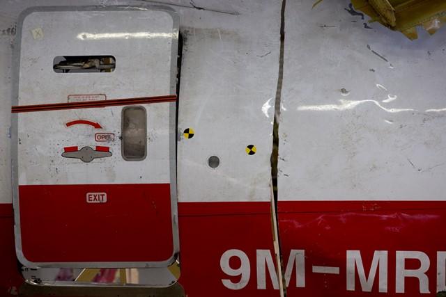 Na snímke registračné číslo lietadla na väčšom kuse trosiek lietadla Boeing 777 letu MH 17 Malazijskych Aerolínii