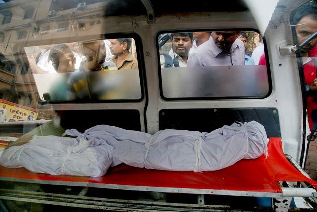 Na snímke ľudia pozerajú do sanitky na telá obetí Inda Hasnaina Warekara v indickom meste Thane