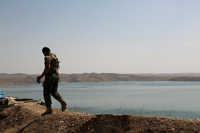 Kurdský bojovník hliadkuje pri Mósulskej priehrade v Chamibarakate pri irackom meste Mósul