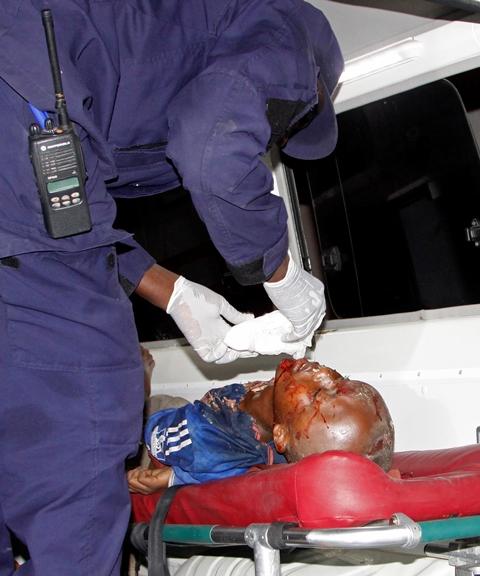Na snímke zdravotník ošetruje zraneného Somálčana po samovražednom bombovom útoku na hotel v Mogadišu