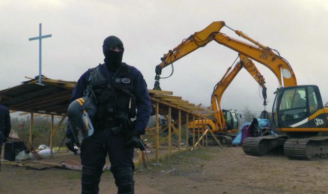 Na videosnímke policajt hliadkuje počas demolácie provizórneho kostola v stanovom tábore na predmestí severofrancúzskeho mesta Calais