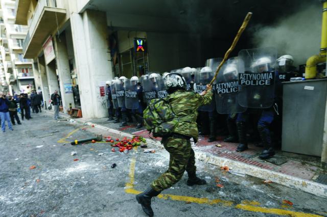 Poľnohospodár s palicou mieri na členov poriadkovej polície pred ministerstvom poľnohospodárstva v Aténach 12. februára 2016. Poľnohospodári z celého Grécka sa zhromaždili v Aténach na dvojdňovej demonštrácii proti vláde a dôchodkovej a daňovej reforme